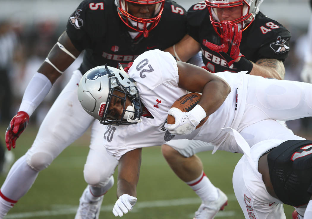 Howard running back Dezmond Wortham (20) is tackled by UNLV linebacker Brian Keyes (5) and linebacker Bailey Laolagi (48) during a football game at Sam Boyd Stadium in Las Vegas on Saturday, Sept. ...