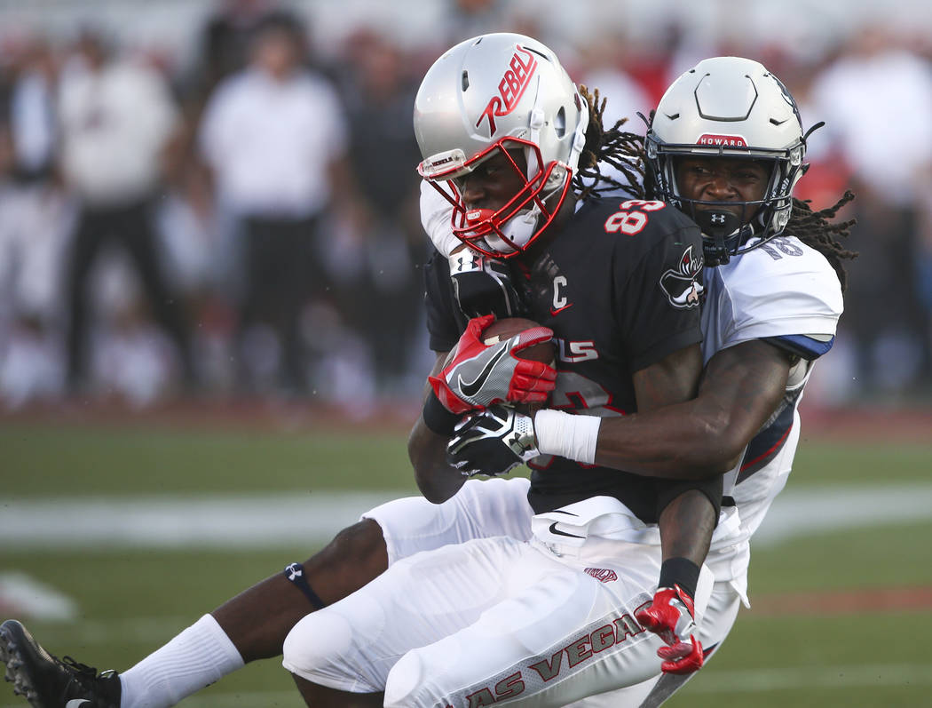 UNLV wide receiver Devonte Boyd (83) is tackled by Howard defensive back Travon Hunt (18) during a football game at Sam Boyd Stadium in Las Vegas on Saturday, Sept. 2, 2017. Chase Stevens Las Vega ...