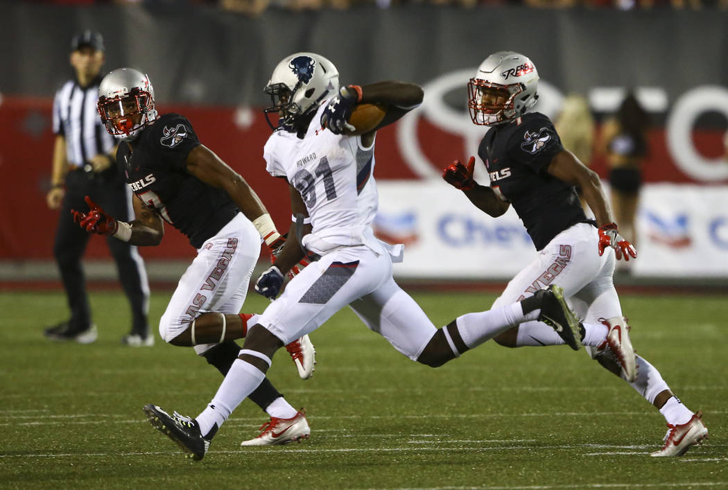 Howard wide receiver Kyle Anthony (81) runs the ball as UNLV defensive back Evan Austrie, left, and wide receiver Jericho Flowers defend during a football game at Sam Boyd Stadium in Las Vegas on  ...
