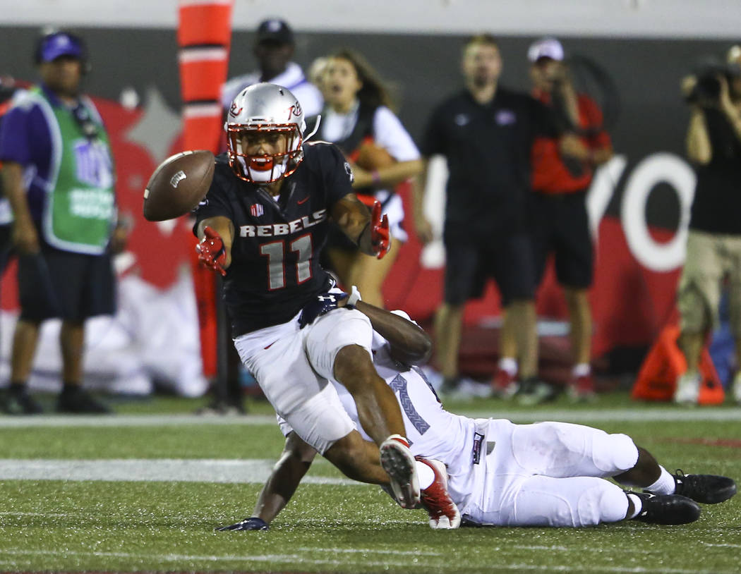 UNLV wide receiver Drew Tejchman (11) loses control of the ball while being tackled by Howard running back Anthony Philyaw during a football game at Sam Boyd Stadium in Las Vegas on Saturday, Sept ...