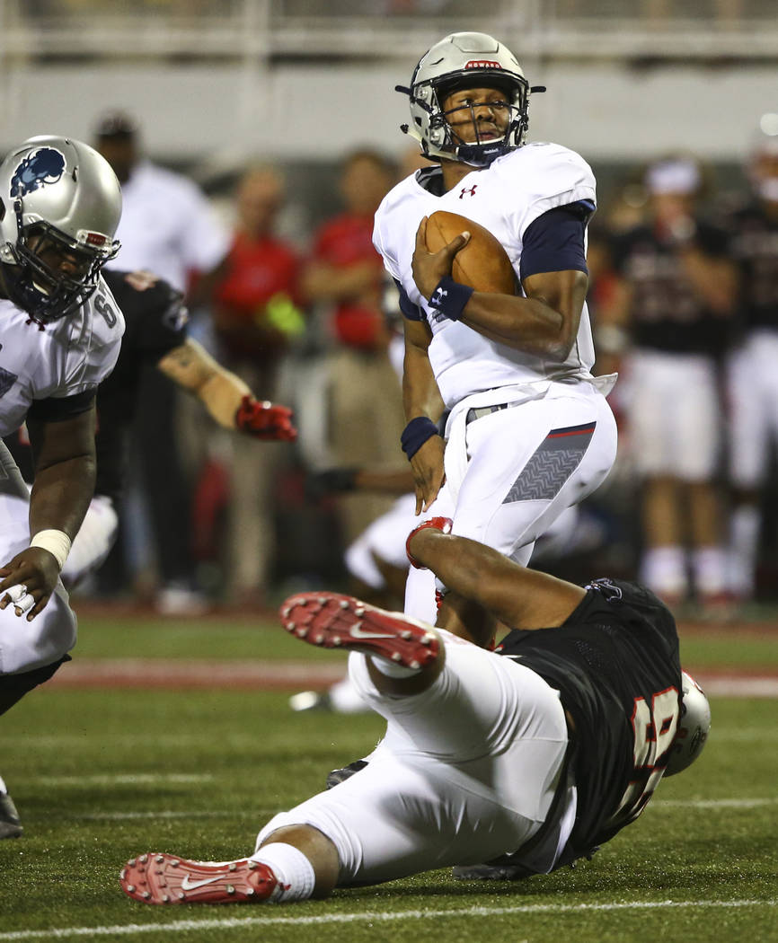 Howard Bison quarterback Caylin Newton (3) is tripped up by UNLV defensive lineman Jason Fao (95) during a football game at Sam Boyd Stadium in Las Vegas on Saturday, Sept. 2, 2017. Chase Stevens  ...