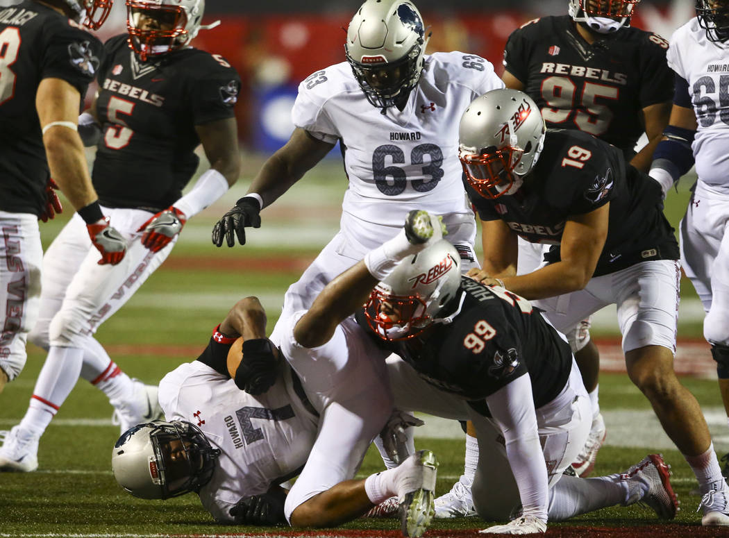 UNLV defensive lineman Mike Hughes Jr. (99) takes down Howard running back Anthony Philyaw (7) during a football game at Sam Boyd Stadium in Las Vegas on Saturday, Sept. 2, 2017. Chase Stevens Las ...