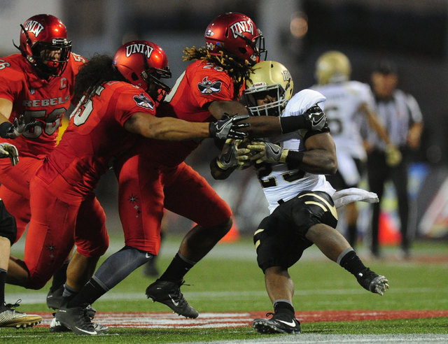 UNLV defensive back LaKeith Walls, middle, and linebacker Tau Lotulelei tackle Idaho running back Aaron Duckworth in the first half of their NCAA college football game against Idaho at Sam Boyd St ...