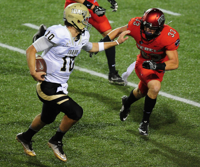 Idaho Vandals quarterback Matt Linehan (10) rushes for a first down as UNLV Rebels defensive back Dalton Baker (33) defends in the first half of their NCAA college football game at Sam Boyd Stadiu ...
