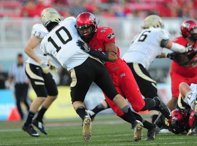 Idaho Vandals quarterback Matt Linehan (10) is knocked down by UNLV Rebels defensive lineman Jeremiah Valoaga (94) in the first half of their NCAA college football game at Sam Boyd Stadium in Hend ...