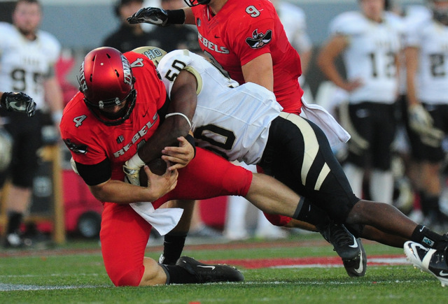 UNLV Rebels quarterback Johnny Stanton (4) is sacked by Idaho Vandals linebacker Ed Hall (50) in the first half of their NCAA college football game at Sam Boyd Stadium in Henderson Saturday, Sept. ...