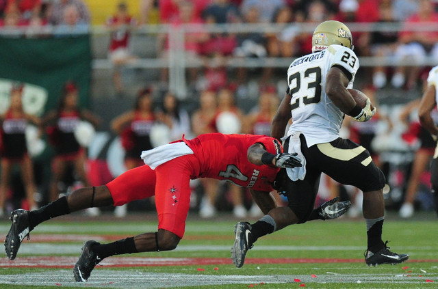 UNLV Rebels defensive back Torry McTyer (4) tackles Idaho Vandals running back Aaron Duckworth (23) in the first half of their NCAA college football game at Sam Boyd Stadium in Henderson Saturday, ...