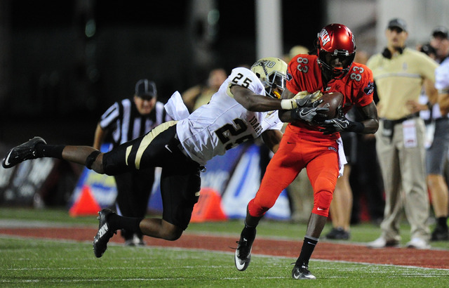 UNLV Rebels wide receiver Devonte Boyd (83) catches a pass as Idaho Vandals safety Desmond Banks (25) defends in the fourth quarter of their NCAA college football game at Sam Boyd Stadium in Hende ...