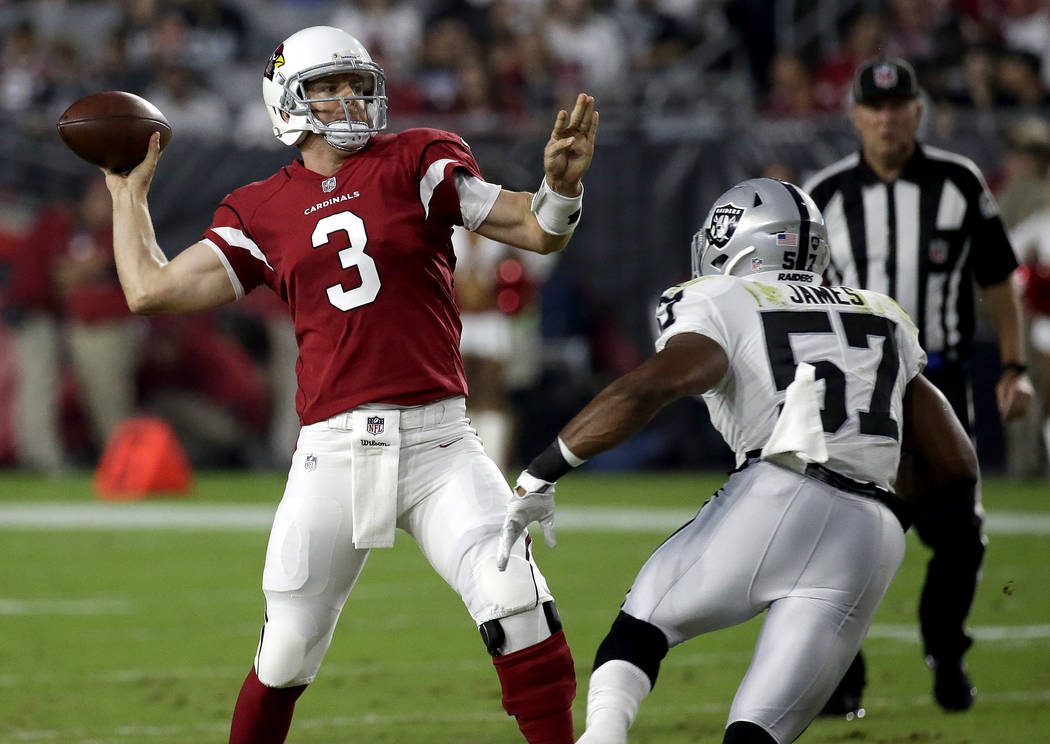 Arizona Cardinals quarterback Carson Palmer (3) throws under pressure from Oakland Raiders middle linebacker Cory James (57) during the first half of an NFL preseason football game, Saturday, Aug. ...