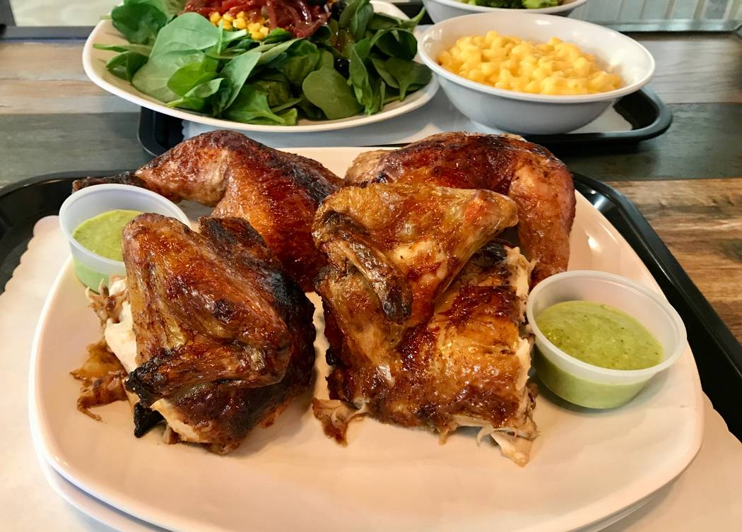 "A whole rotisserie chicken with a side of ""green sauce"" at Rotisserie Chicken. (Madelyn Reese/View) @MadelynGReese"