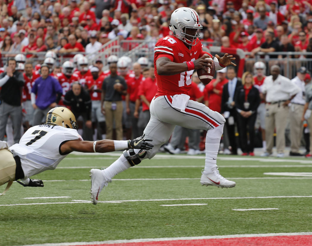 Ohio State quarterback J.T. Barrett, right, scores a touchdown past Army defensive back Jaylon McClinton during the first half of an NCAA college football game Saturday, Sept. 16, 2017, in Columbu ...