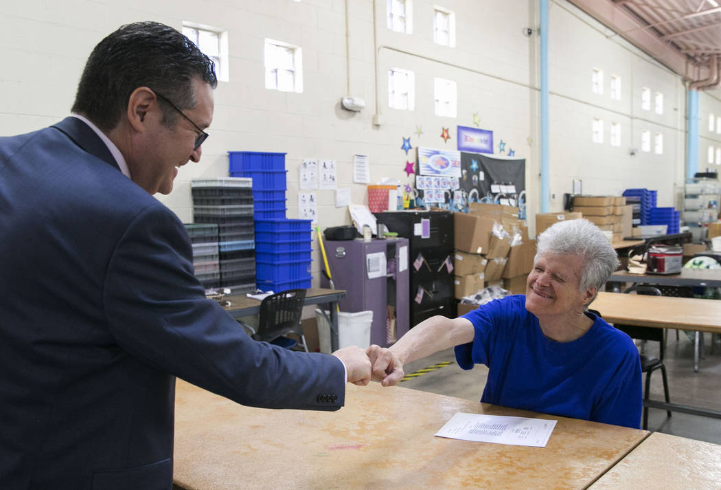 Opportunity Village's Vice President of Philanthropy, Adam Joseph, left, fist-bumps Douglas G., at Opportunity Village on Wednesday, Aug. 30, 2017, in Las Vegas. (Bizuayehu Tesfaye/Las Vegas Revie ...