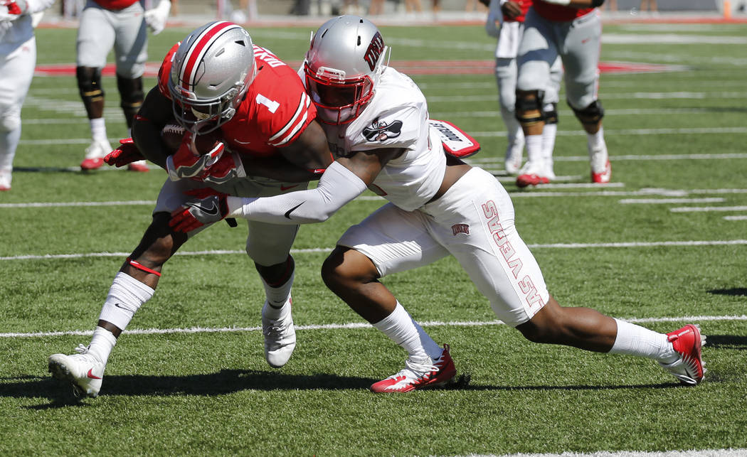 Ohio State receiver Johnnie Dixon, left, crosses the goal line as UNLV defensive back Chauncey Scissum tries to make the tackle during the first half of an NCAA college football game Saturday, Sep ...