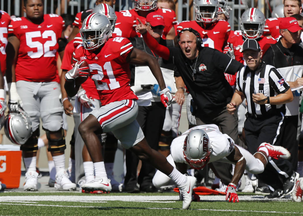 Ohio State receiver Parris Campbell, left, escapes the grasp of UNLV linebacker Gabe McCoy on his way to scoring a touchdown during the first half of an NCAA college football game Saturday, Sept.  ...