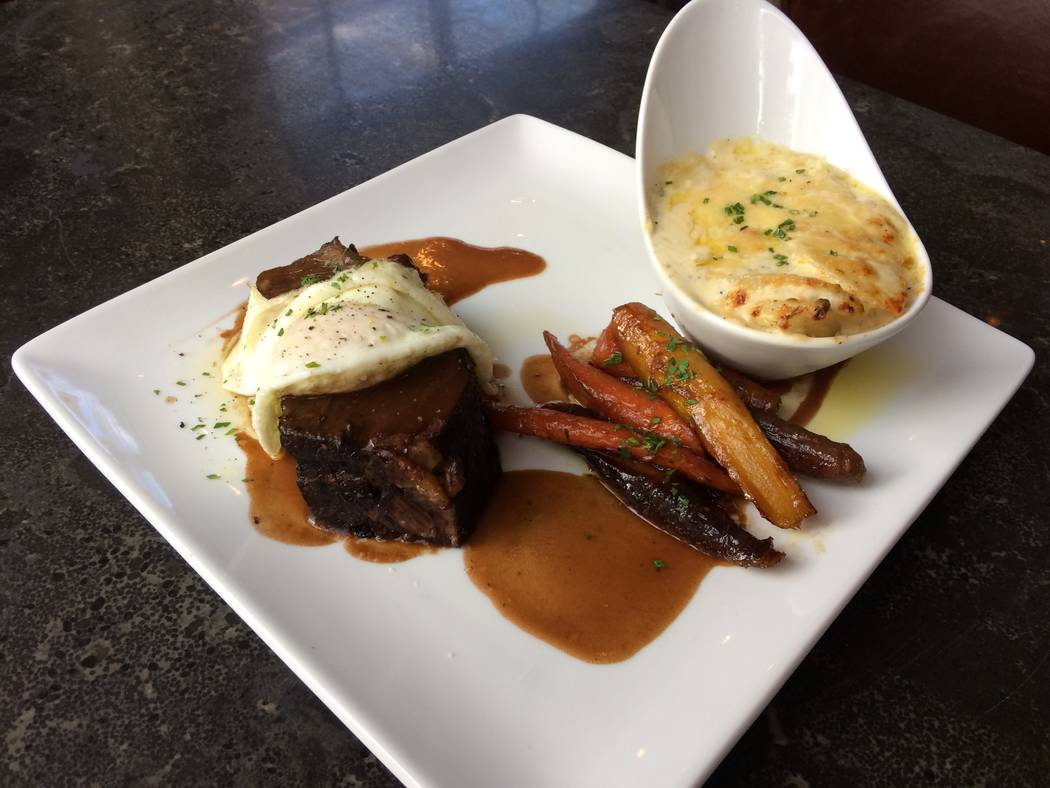 Braised Angus short rib has New York cheddar potato gratin, honey and garlic braised carrots, over easy egg with a bordelaise sauce. (Jan Hogan/View)