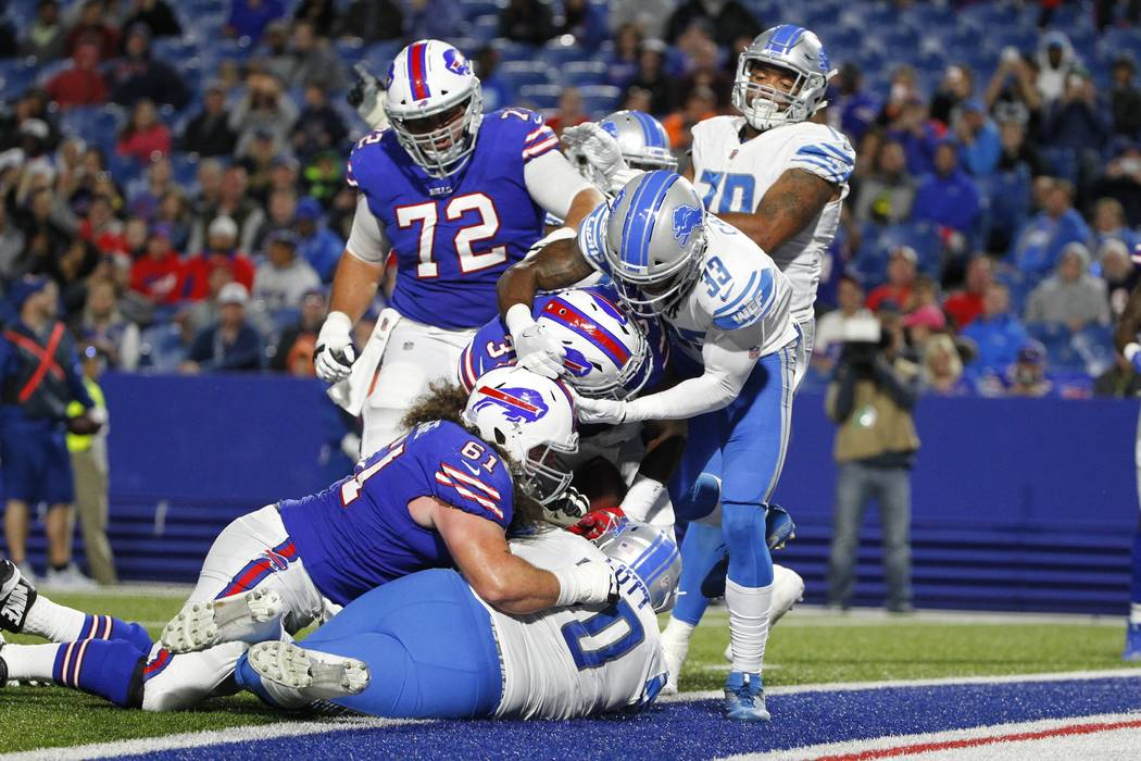 Detroit Lions' Alex Carter (33) and Corey Robinson (70) tackle Buffalo Bills' Jordan Johnson (39) in the end zone after Johnson scored a touchdown during the second half of a preseason NFL footbal ...