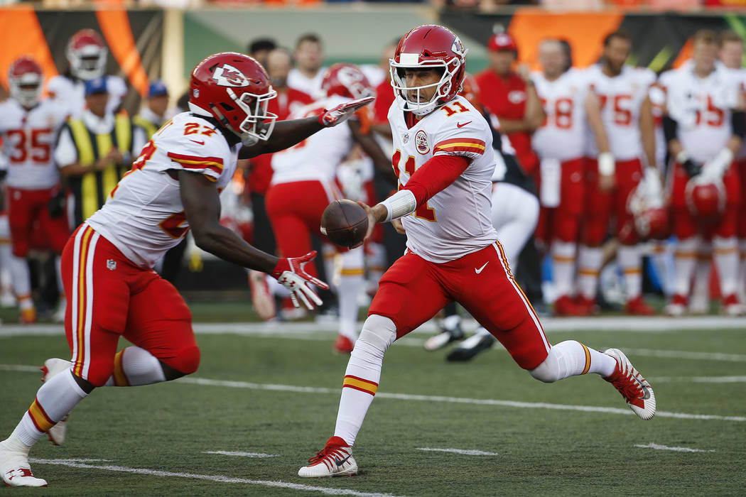 Kansas City Chiefs quarterback Alex Smith (11) hands off the ball to running back Kareem :Hunt (27) during the first half of an NFL preseason football game against the Cincinnati Bengals, Saturday ...