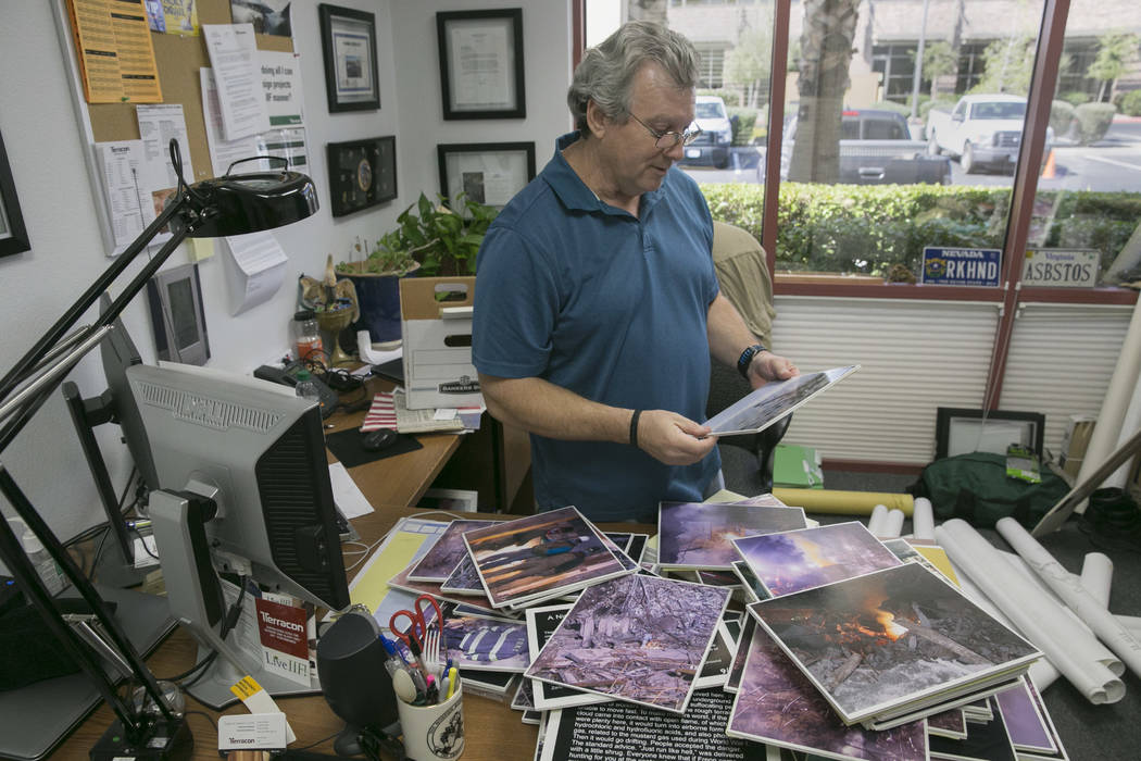 Duane Matters looks through photos he took while he worked as a part of  the World Trade Center's emergency clean up crew in his office in Las Vegas, Friday, Sept. 1, 2017.  Gabriella Angotti-Jone ...