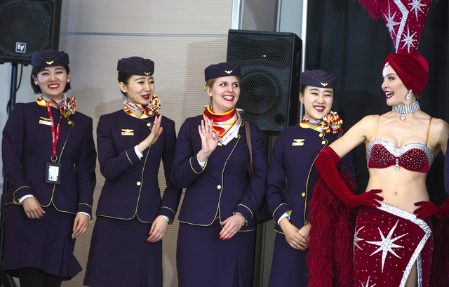 Flight attendants from Hainan Airlines wave during an inaugural flight reception at McCarran International Airport on Friday, Dec. 2, 2016 celebrating the airline's first nonstop flight from China ...