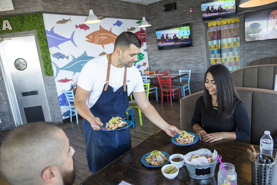 Kitchen manager Erik Esparza, center, delivers tostadas to Eliazar Marin, left, and Delia Holguin during lunch at Cevicheria El Diamante located at 2457 East Tropicana Avenue on Monday, Sept. 11,  ...