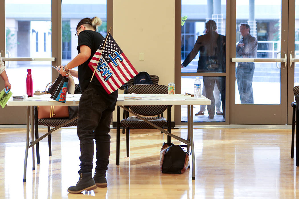 "With an American flag that says ""I Dream"" sticking out of their pocket, an attendee picks up papers during an informative event on Deferred Action for Childhood Arrivals at East  ..."
