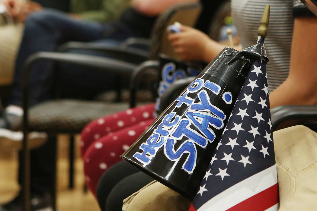 "A megaphone that says ""Here to stay!"" taped on an American flag rests on an attendees's leg during an informative event on Deferred Action for Childhood Arrivals at East Las Vegas Community Center ..."