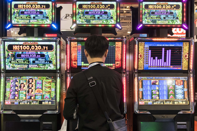 An attendee stands in front of electronic slot machines at the Macao Gaming Show in Macau, China, on Nov. 17, 2015. (Bloomberg/Xaume Olleros)