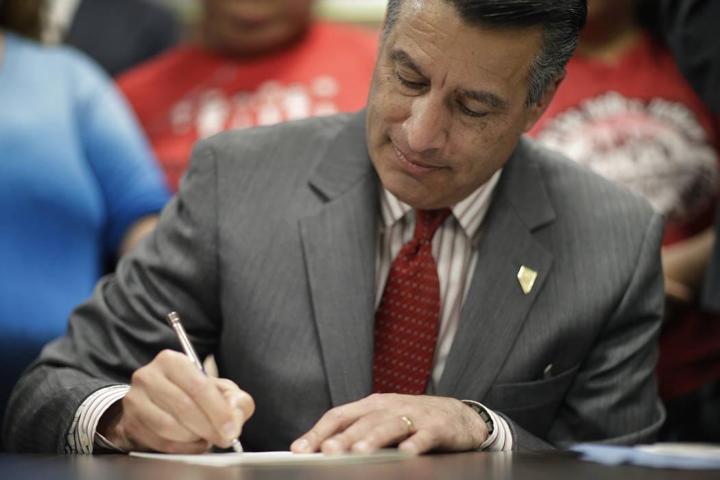 Nevada Gov. Brian Sandoval signs a bill during a signing ceremony Thursday, June 15, 2017, in North Las Vegas. (John Locher/AP)