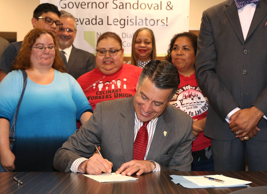 Gov. Brian Sandoval, signs insulin bill, that requires pharmaceutical companies to release insulin prices, into law at Culinary Health Center on Thursday, June 15, 2017, in Las Vegas. (Bizuayehu T ...