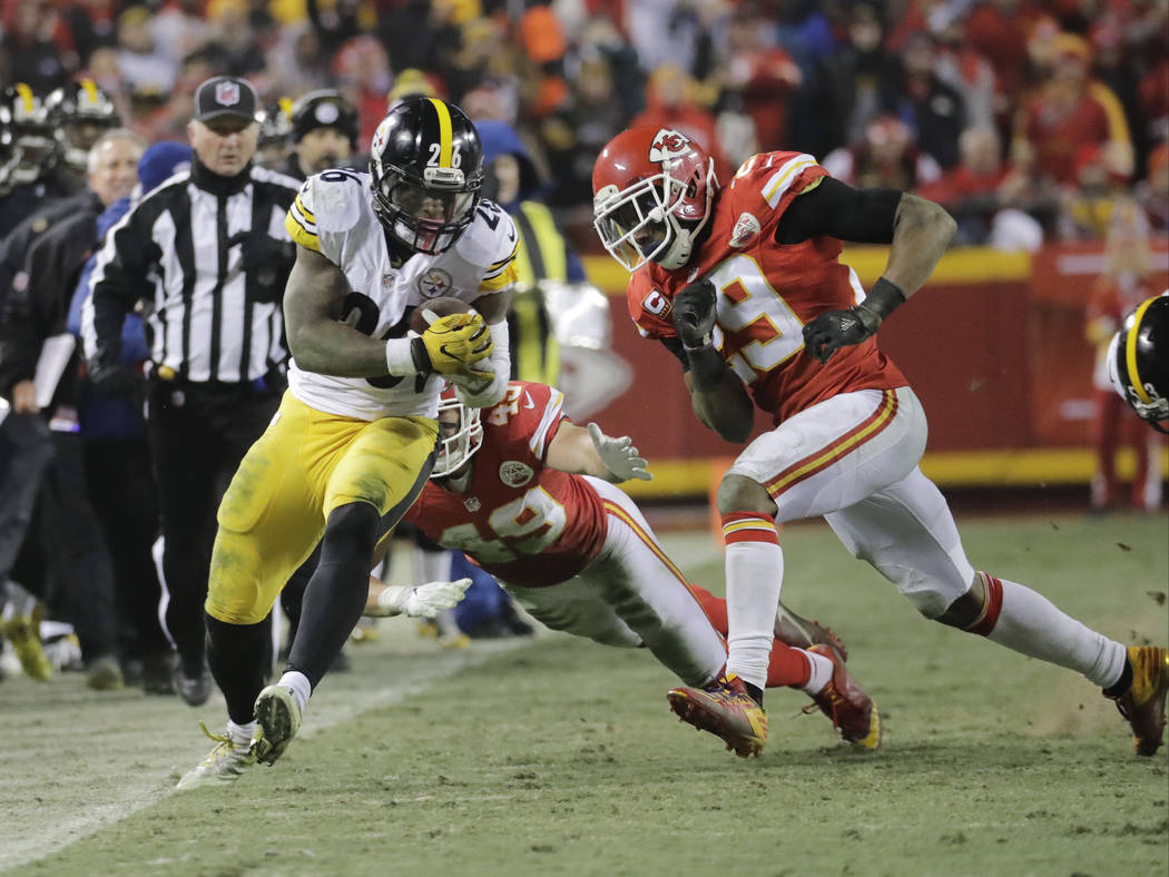 Pittsburgh Steelers running back Le'Veon Bell (26) is tackled by Kansas City Chiefs defensive back Daniel Sorensen (49 and strong safety Eric Berry (29) during the first half of an NFL divisional  ...