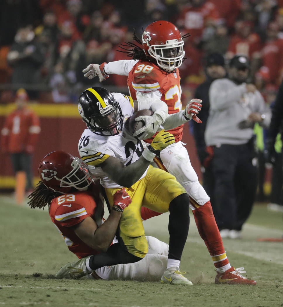Pittsburgh Steelers running back Le'Veon Bell (26) is tackled by Kansas City Chiefs inside linebacker Ramik Wilson (53) during the second half of an NFL divisional playoff football game Sunday, Ja ...