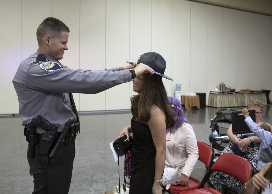 Reed Toone, of Las Vegas, places  his hat on his wife January after his graduation ceremony of Nevada Highway Patrol Advanced Academy 77 at the South Point in Las Vegas on Friday, Sept. 1, 2017. B ...