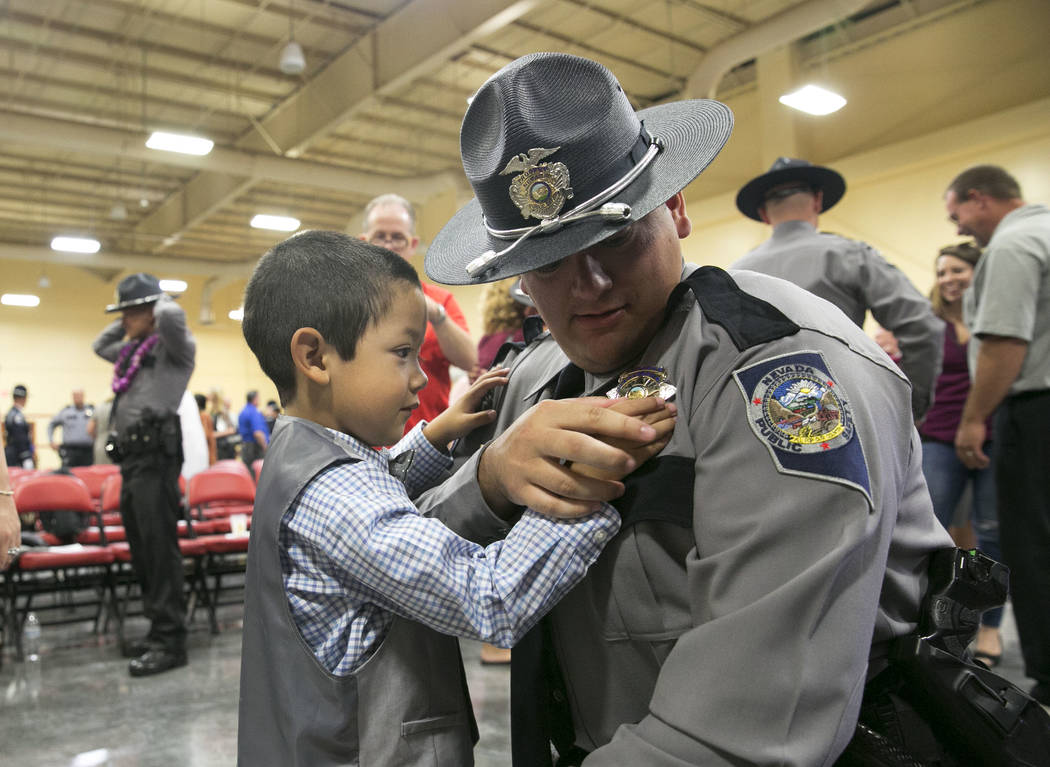 Justin Branske of Beatty, Nev. shares a moment with his son Michael, 4, after his graduation ceremony of Nevada Highway Patrol Advanced Academy 77 at the South Point in Las Vegas on Friday, Sept.  ...