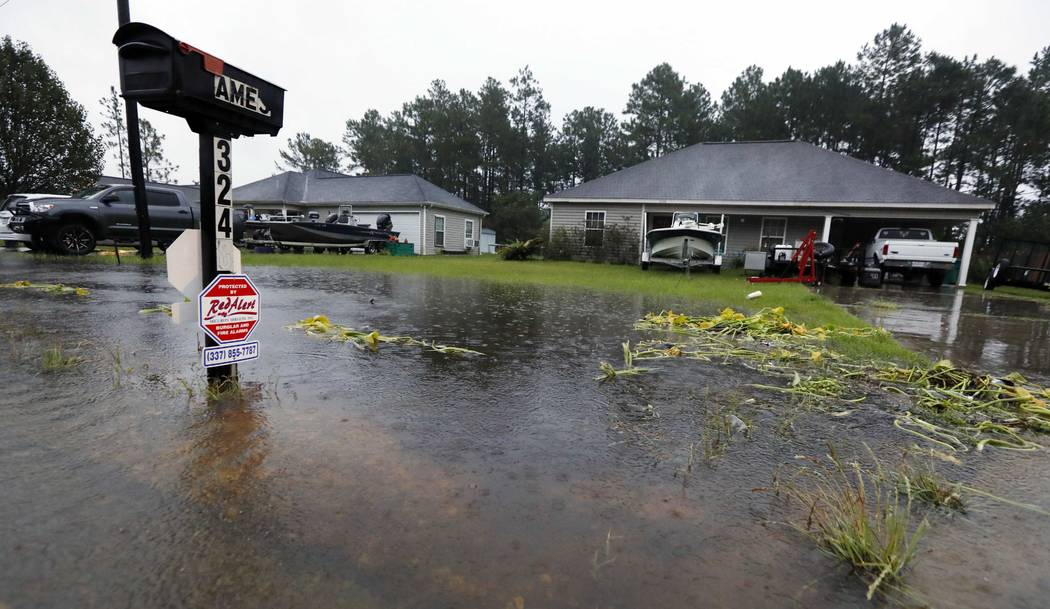 Rising waters threaten homes along North Perkins Ferry Road in Moss Bluff, La., near Lake Charles, La., as a constant rain from Tropical Storm Harvey falls, Monday, Aug. 28, 2017. (AP Photo/Rogeli ...