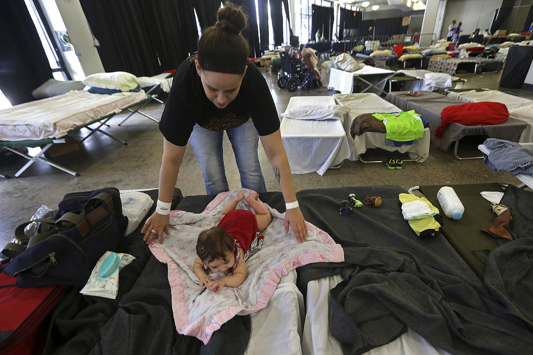 Katrina Johnson, an evacuee from Tropical Storm Harvey, spreads a blanket for her four month old daughter Blakely Knaus, at an evacuation shelter in the Lake Charles Civic Center, for those displa ...