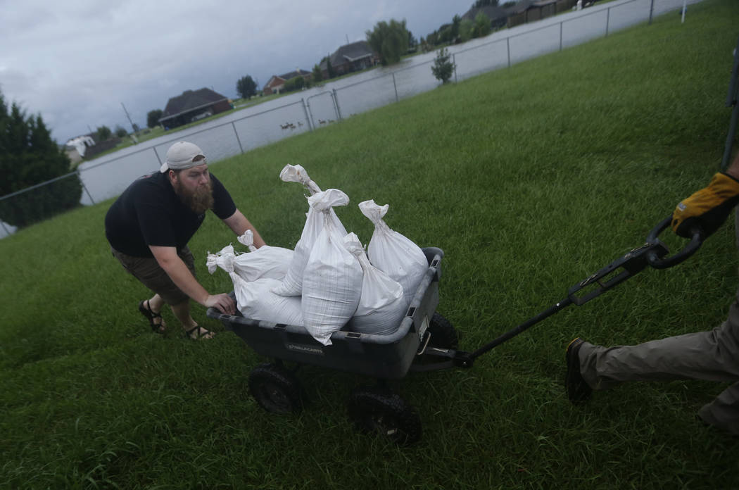 Cody McLemore pushes a wagon filled with sandbags as he fortifies his house in the flooded Clearfield Farm subdivision, in anticipation of more flooding from Tropical Storm Harvey, in Lake Charles ...