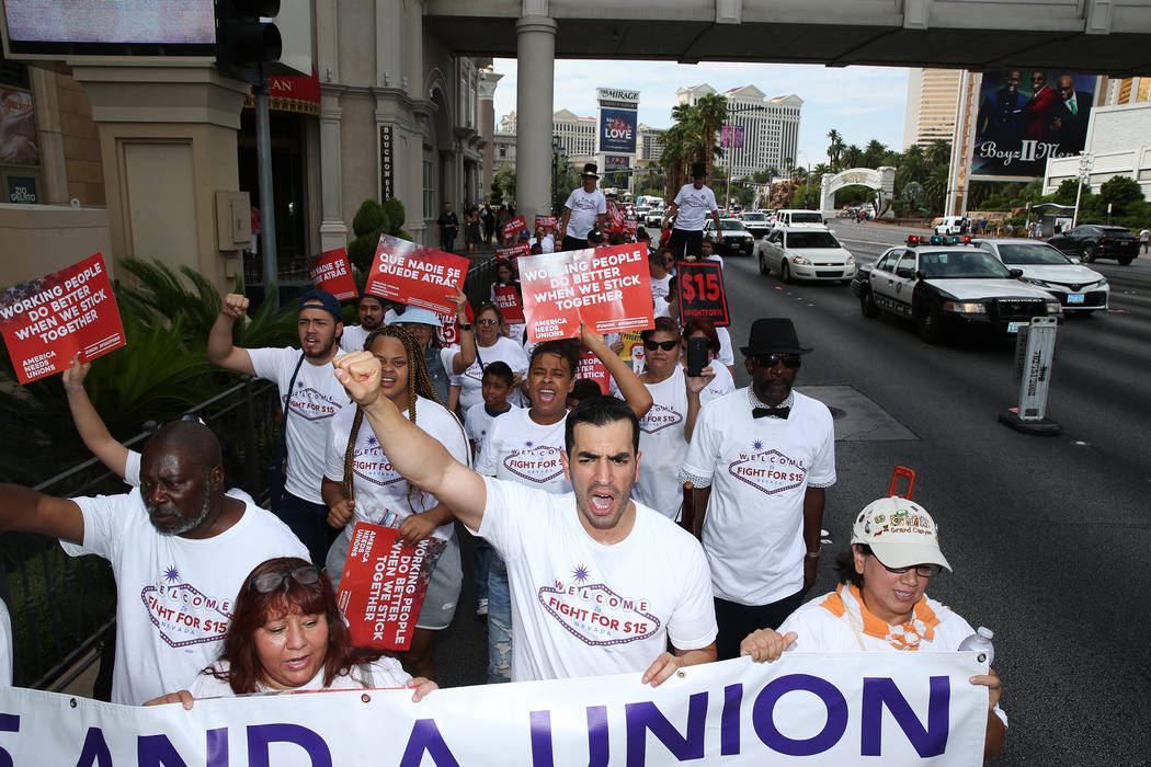 People including U.S. Rep. Ruben Kihuen, D-Nev., second from right, participate during a Fight for $15 rally and march on the Las Vegas Strip in Las Vegas, on Monday, Sept. 4, 2017. Erik Verduzco  ...