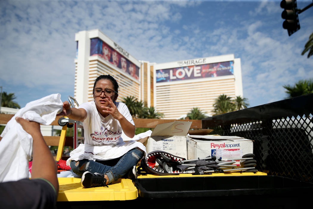 A woman who declined to be identified hands out shirts for attendees of a Fight for $15 rally and march at the McDonald's near Harrah's hotel-casino in Las Vegas, on Monday, Sept. 4, ...