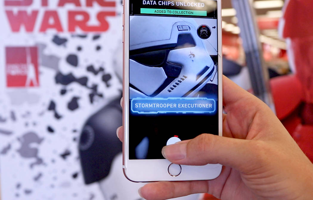Using the Star Wars mobile app, users can scan cardboard cutouts of characters to unlock special features. A user scans a new kind of Stormtrooper at a North Las Vegas Target, Friday, Sept. 1, 201 ...