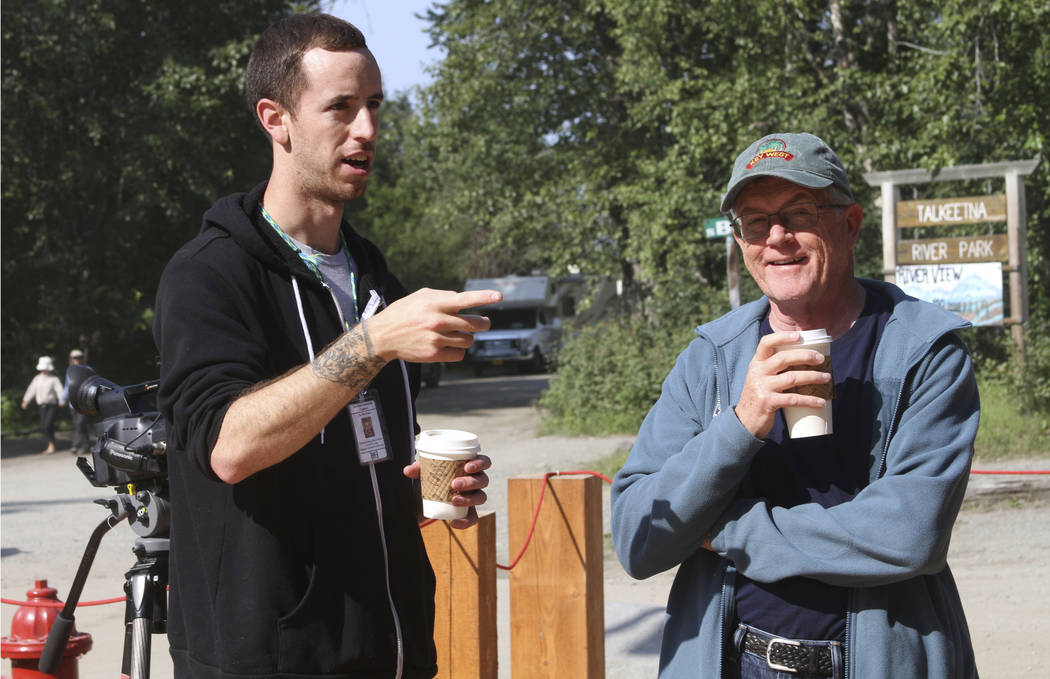 Joe McAneney, left, co-owner of The High Expedition Co. in Talkeetna, Alaska, talks to tourist Jeff White, who lives near Louisville, Kentucky, in July. (AP Photo/Mark Thiessen)