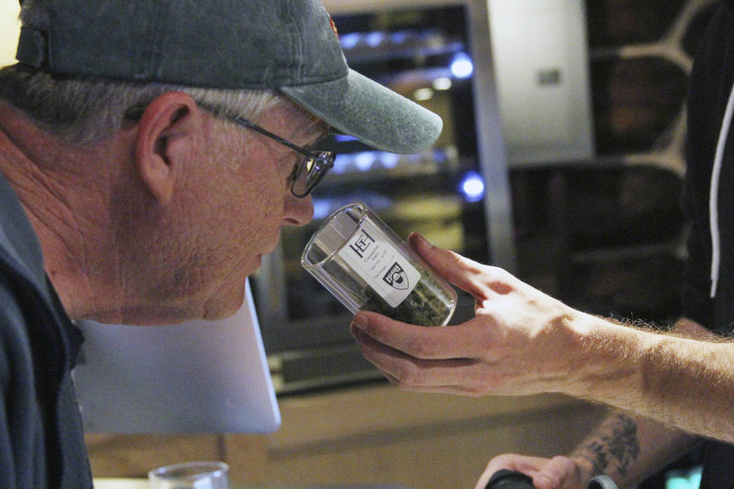 Tourist Jeff White, who lives near Louisville, Kentucky, smells the marijuana for sale at The High Expedition Co. in Talkeetna, Alaska, in July. (AP Photo/Mark Thiessen)