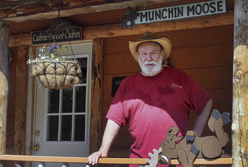 Owner Mike Stoltz poses for a photo in front of a cabin at his Meandering Moose Lodging in Talkeetna, Alaska, in July. (AP Photo/Mark Thiessen)