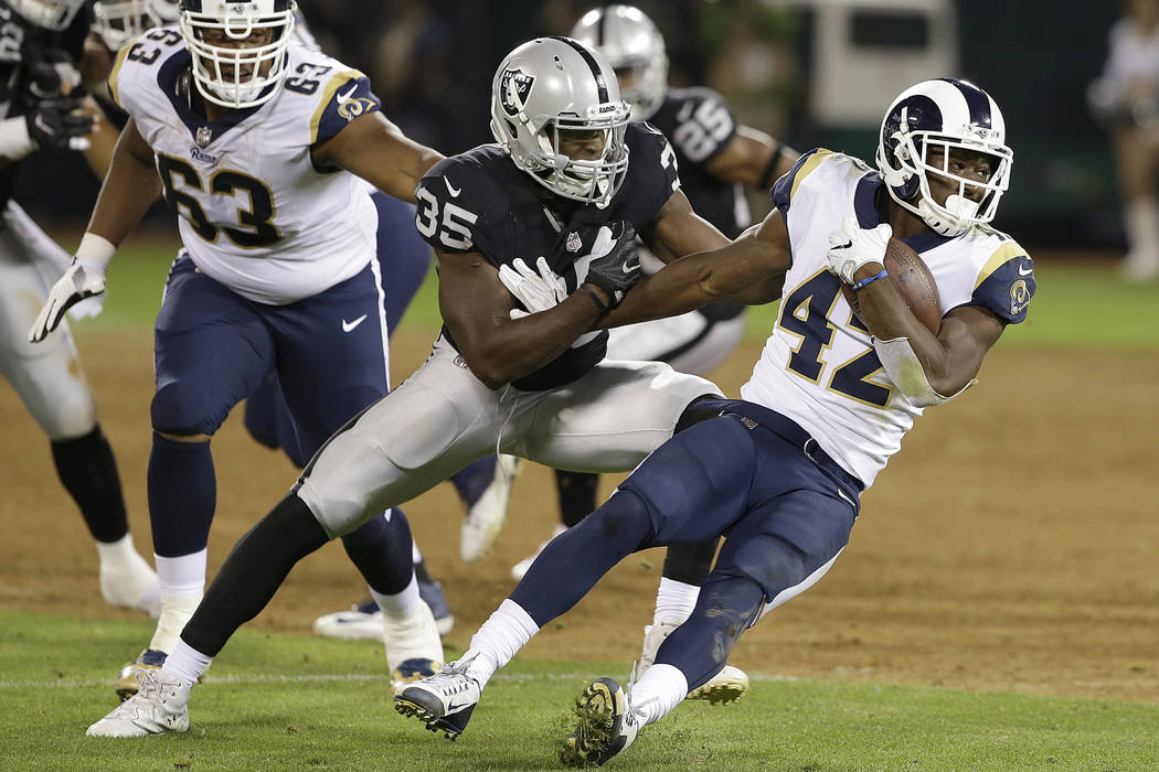 Los Angeles Rams running back Justin Davis (42) runs from Oakland Raiders linebacker Nicholas Morrow (35) during the second half of an NFL preseason football game in Oakland, Calif., Saturday, Aug ...