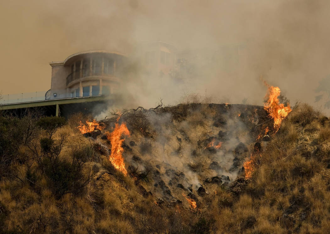 Firefighters battle a brushfire on a hillside near a home in Burbank Calif. on Saturday Sept. 2 2017