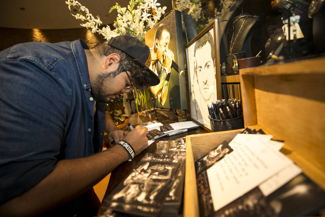 Linkin Park fan Charlie Vargas of Las Vegas leaves a note at a memorial for singer and songwriter Chester Bennington at Club Tattoo inside Planet Hollywood on Saturday, Sept. 2, 2017, in Las Vegas ...