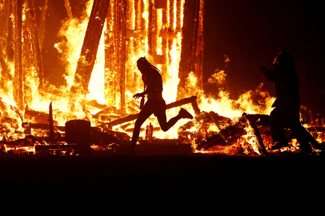 """A Burning Man participant evades a chasing firefighter and runs into the flames of the """"Man Burn"""" after evading the attempted tackles of multiple rangers and law enforcement personnel at the annua ..."""