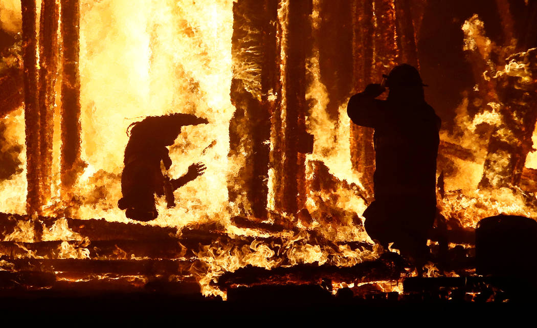 """A Burning Man participant, left, evades a chasing firefighter and falls into the flames of the """"Man Burn"""" after evading the attempted tackles of multiple rangers and law enforcement personnel at t ..."""