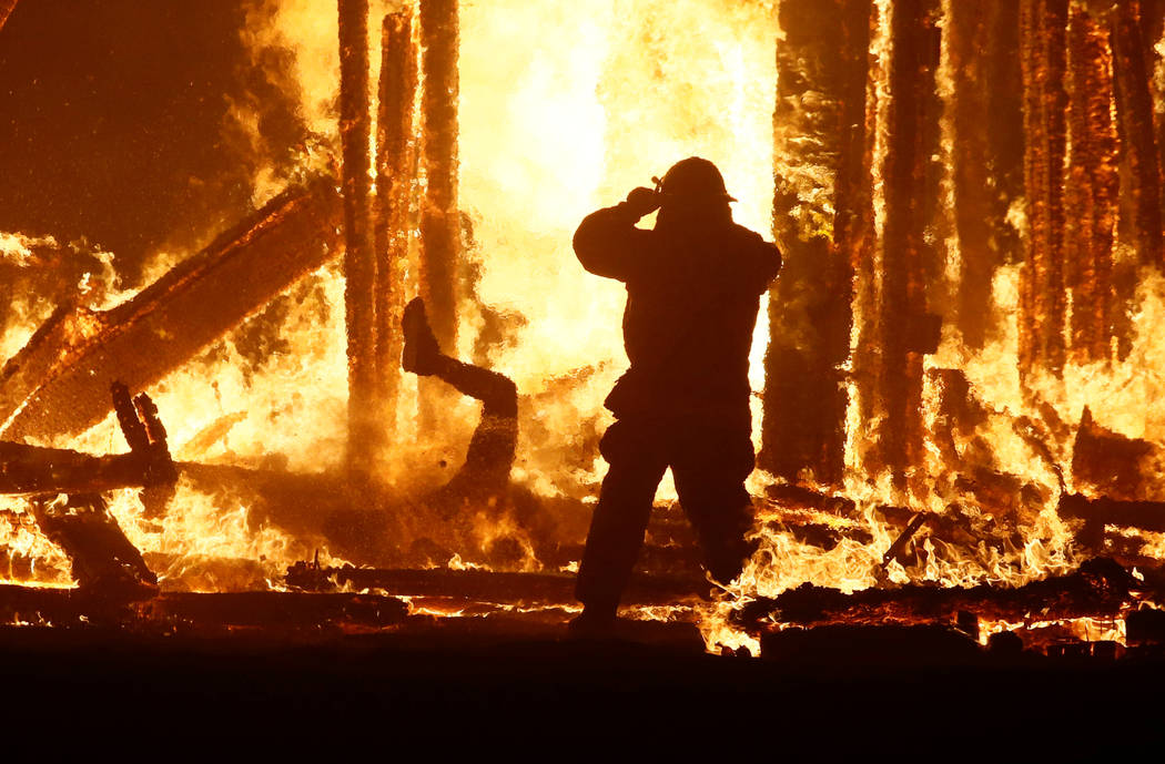 "ATTENTION EDITORS - VISUAL COVERAGE OF SCENES OF INJURY OR DEATH A firefighter watches as a Burning Man participant (L) evades a chasing firefighter and falls into the flames of the ""Man Burn"" aft ..."