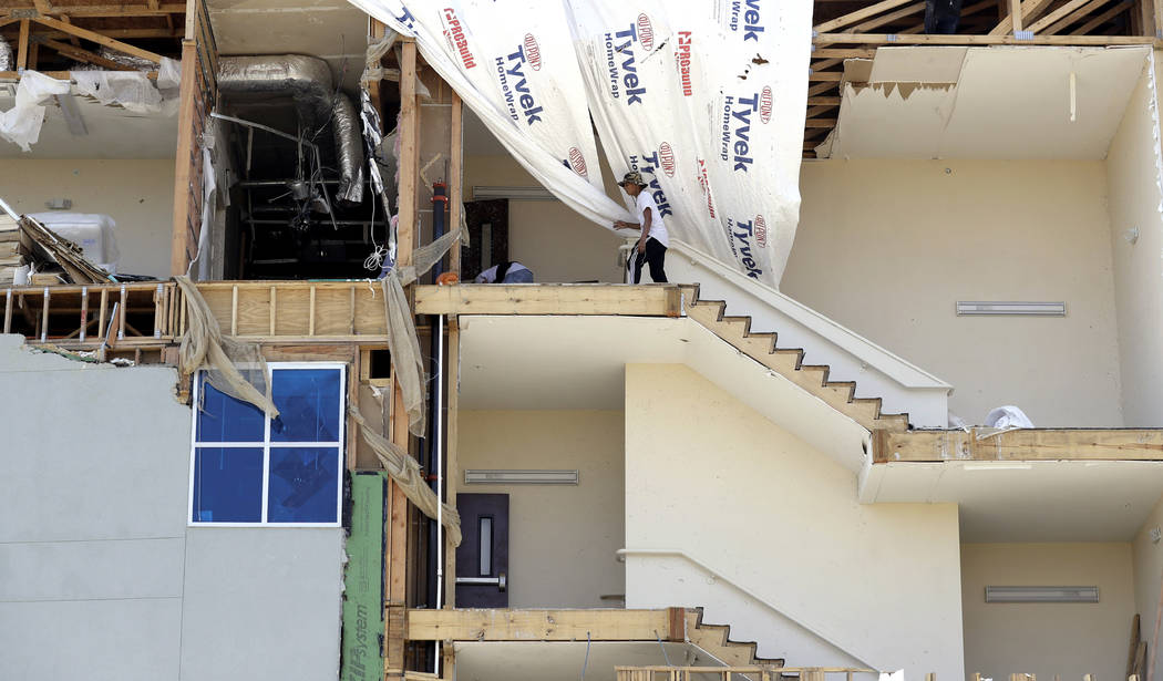 Workers pick up debris in a staircase of a four-story hotel exposed when the wall fell during Hurricane Harvey, Saturday, Sept. 2, 2017, in Rockport, Texas. (Eric Gay/AP)