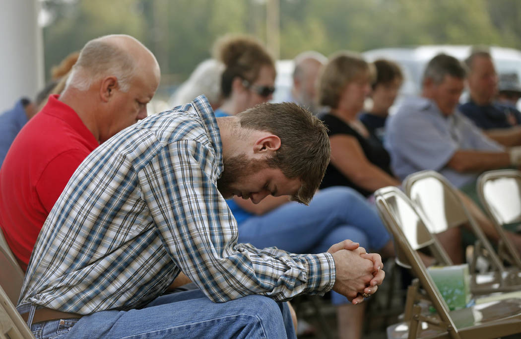 Jacob Hamilton bows his head in prayer as members of the Pine Forest Baptist Church hold Sunday services in the parking lot outside their damaged church, in the aftermath of Tropical Storm Harvey  ...